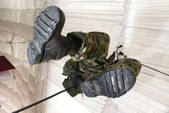 Soldier hanging from ceiling. A shot of a soldier in green camouflage uniform suspended from the ceiling and his boots are visible. Ceiling is a tent structure stock image