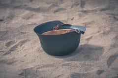 Soldier helmet. Old soldier helmet upside down on sand ground royalty free stock image