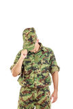 Soldier with hidden face in green camouflage uniform covers face Stock Photo