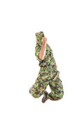 Soldier with hidden face in green camouflage uniform and hat jum Stock Photography