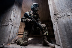 Soldier hiding in a concrete behind cover where kneeling in the doorway with a gun in his hand. Military man in camouflage and wearing a mask on his knees in the Royalty Free Stock Photos
