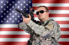 Soldier with his assault rifle. On flag background Royalty Free Stock Photography