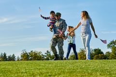 Soldier with his family are walking with usa flags. Father came back grou US army and wealking with his daughters and wife on the grass stock photography
