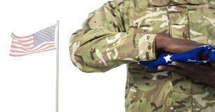 Soldier holding the american flag in front of white background Royalty Free Stock Photos