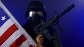 Soldier holding assault rifle in smoky haze. Soldier in army fatigues wearing gas mask holding assault rifle in haze of blue smoke stock video footage