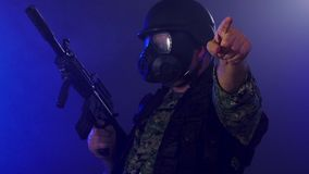Soldier holding assault rifle in smoky haze. Soldier in army fatigues wearing gas mask holding assault rifle and signaling direction with hand in haze of blue stock video footage