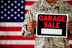 Soldier: Holding Blank Garage Sale Sign. Series with an anonymous African-American soldier on a United States Flag background Royalty Free Stock Images