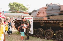 Soldier holding a boy with a war tank behind. Campo Grande, Brazil - September 09, 2018: Soldier holding a boy with a war tank behind to take a photo at the royalty free stock photos
