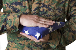 Soldier Holding Flag. A soldier in camouflage holds a flag Royalty Free Stock Photo
