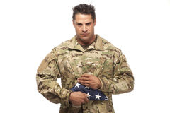 Soldier holding folded American flag Stock Photography