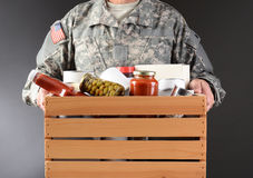 Soldier Holding Food Drive Box. Closeup of a soldier in fatigues holding a wooden box full of canned and packaged food for a holiday charity drive. Horizontal royalty free stock photo