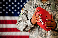 Soldier: Holding a Football. Series with an anonymous African-American soldier on a United States Flag background stock images
