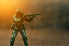 Soldier holding a gun aimed at the enemy. Green Soldier holding a gun aimed at the enemy Royalty Free Stock Photo