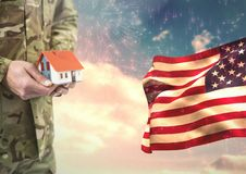 Soldier holding a little house close to the american flag Stock Photo