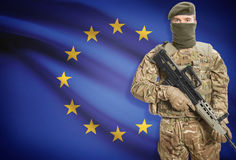 Soldier holding machine gun with flag on background series - European Union - EU Royalty Free Stock Images