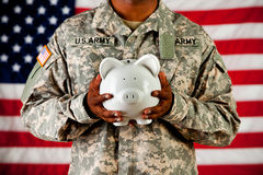 Soldier: Holding a Piggy Bank. Series with an anonymous African-American soldier on a United States Flag background Stock Images
