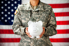Soldier: Holding a Piggy Bank. Series with a female as a solidier in an United States Army uniform.  Numerous props convey a variety of concepts Royalty Free Stock Photography