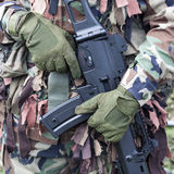 Soldier holding weapon. Hands of a soldier in camouflage uniform holding weapon Royalty Free Stock Photo