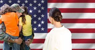 Soldier hugging his kids and mother looking at them. Against american flag Stock Photography