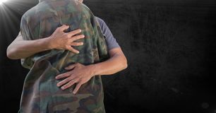Soldier hugging mid section against black background and flare stock photos