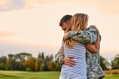 Soldier is hugging a woman outdoor. stock image