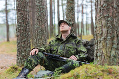 Soldier or hunter with gun sleeping in forest. Hunting, war, army and people concept - young soldier, ranger or hunter with gun sitting and sleeping in forest royalty free stock image