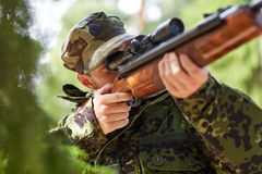 Soldier or hunter shooting with gun in forest. Hunting, war, army and people concept - young soldier, ranger or hunter with gun walking in forest royalty free stock photography