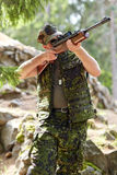 Soldier or hunter shooting with gun in forest Royalty Free Stock Images