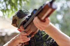 Soldier or hunter shooting with gun in forest Royalty Free Stock Image