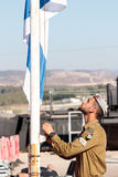 Soldier of the IDF raices the flag at the evening formation in Nahariya, Israel Royalty Free Stock Image
