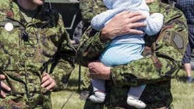 Soldier and kid. Soldier reunited with his baby on a sunny day on a sunny day with military equipment on the background. concept of salvation and liberation royalty free stock image