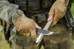 Soldier with a knife cut a wooden stick Stock Photos