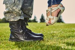 Soldier in leather boots and girl in sandals. Standing on the grass, lifting up daugther royalty free stock photo