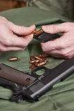 Soldier load ammo in clip Colt. Soldier load ammo in the clip Colt Stock Photography