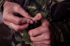 Soldier loading a 9mm caliber cartridge. On a military shooting range Stock Image