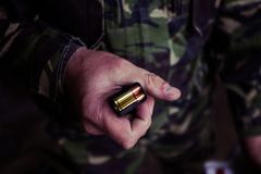 Soldier loading a 9mm caliber cartridge. On a military shooting range Royalty Free Stock Photos