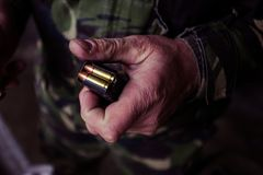 Soldier loading a 9mm caliber cartridge. On a military shooting range Royalty Free Stock Photo