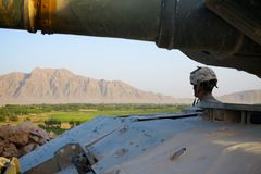 Soldier looking at Afghan Landscape. A US soldier stands next to a tank and looks out over the landscape of Kandahar Province, Afghanistan Stock Photo