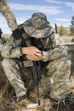 Soldier Looking Down. Full length of an armed soldier looking down while sitting Stock Images