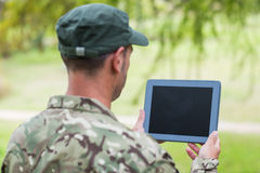Soldier looking at tablet pc in park. On a sunny day stock photo