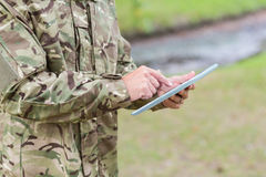 Soldier looking at tablet pc in park Royalty Free Stock Images