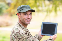 Soldier looking at tablet pc in park Royalty Free Stock Photos