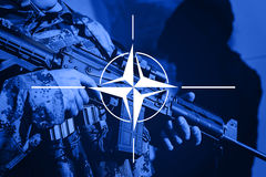 Soldier with machine gun with flag of NAtO Alliance. Flag stock images
