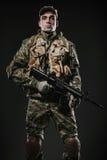 Soldier man hold Machine gun on a  dark background Stock Photography