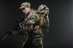 Soldier man hold Machine gun on a  dark background. Military, war, conflict, soldiers - Special forces soldier man hold Machine gun on a  dark background Stock Photography