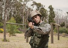 Soldier man holding a weapon against field Royalty Free Stock Photography