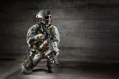 Soldier with mask rifle and backpack. On dark background Stock Images