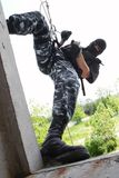 Soldier in mask on rope targeting through window Royalty Free Stock Image