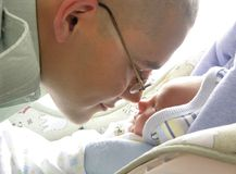 Soldier Meets Son. A father soldier meets his newborn son for the first time at 5 days of life Stock Image