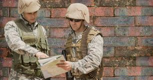 Soldier men looking at a map against a brick wall stock images